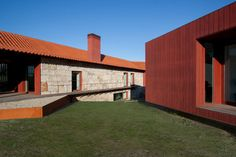 Pitágoras Arquitectos adds red timber wing to stone farmhouse in rural Portugal.