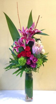 Contemporary arrangement of grouped roses, protea king, lilies, hydrangea, trachelium, acordeon, selloum and bamboo. In burgundy, purple, pink, white, red and green.