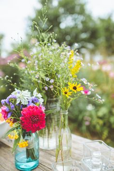 wildflowers in bottles and mason jars, photo by Paper Antler http://ruffledblog.com/jackson-meadow-wedding #centerpieces #flowers