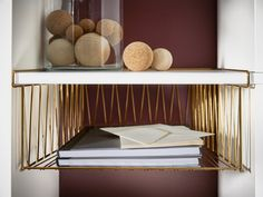 A brass-colored wire basket with notebooks, attached to KALLAX shelving unit.