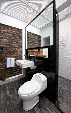 Living in Bogotá - Colombia. Piso de pizarra y muros existentes de ladrillo bajo la marquesina y el entramado de varillas en el baño con enchape negro.