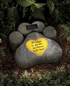 """This Solar Pet Memorial Statue celebrates the life of your favorite sidekick. The statue charges in the sun and lights up the heart holding the sentiment at dusk. On/off button. Paw Print, 9""""W x 3""""D x"""