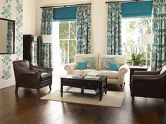 This living room design features dark stained floors and coffee table, rich brown leather armchairs off-set by light cream walls and sofa accented with the lovely complimentary colour of turquoise blue in the patterned floor to ceiling curtains, feature wall and cushions. Altogether it creates a subtle and tranquil effect.