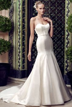 Casablanca Bridal - Camilla. Strapless Duchess Satin trumpet silhouette gown has modified sweetheart front and back necklines. The of the gown has a pleated panel at the center of the back neckline and matching fabric buttons go down the entire length of the skirt and train. Detachable beaded ribbon sash adds sparkle to the natural waist.