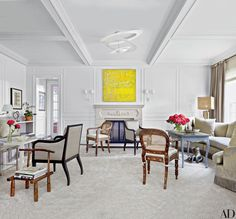 An array of seating from VW Home animates the living room; the ceiling light is by Giuseppe Maurizio Scutellà for Artemide, the sconces are a Vicente Wolf design from VW Home, and the painting over the fireplace is by Andrew Bick | archdigest.com