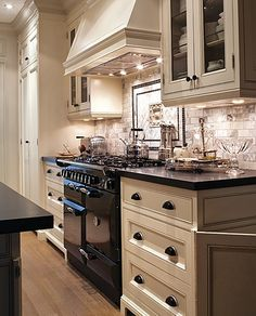 kitchen...  Black and white kitchen. Marble subway tile back splash. Glazed cabinets. Black appliances, stove. Beautiful