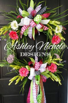 This is a beautiful and colorful wreath with sprayed grapevine, greenery, flowers, and brightly colored bows.