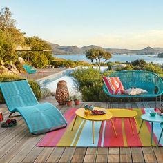 Un salon de jardin gypsie et coloré avec banquette, transat et tapis multicolore sur une terrasse qui longe une piscine.
