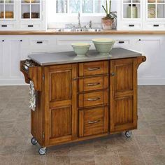This Kitchen Cart by Mix and Match is large in size with two cabinets and four utility drawers that provide enclosed storage. Made of solid wood, the kitchen cart features a rich Dark Cottage Oak Stained base and a stainless steel top and measures 52-1/2 inch W x 18 inch D x 36 inch H.