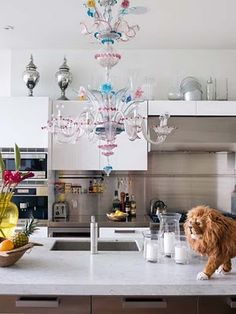 Novogratz. Love the use of the Murano chandelier in a very utilitarian kitchen.