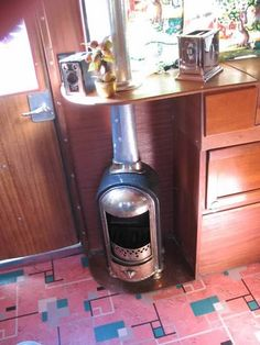 This mini-stove includes a fireproof table around its stovepipe so no overhead space is wasted. | 1937 Covered Wagon Restored (image only) | Tiny Homes