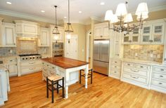 This white kitchen features light honey hardwood flooring and a near-matching island countertop.
