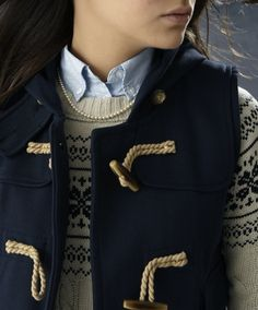 Love the vest with the toggle buttons over the fairisle patterned sweater.