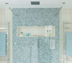 Shower with blue mosaic tile and rainfall showerhead - maybe a little too modern for me, but ahh!  The light, color, tile, and glass!  Gorgeous.