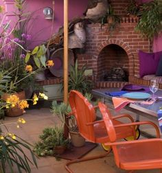 vibrant outdoor space complete with fireplace, purple walls and pillows paired with orange chairs..  very inviting space