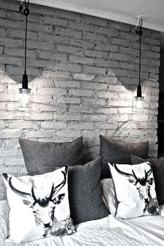 love the deer pillows and the two small black dropped pendant lights against the brick wall!