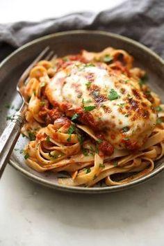 poulet à la mozzarella et à la tomate servi dans une assiette et avec une fourchette en gros plan