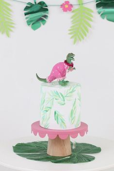How to style a Pink Dinosaur Party for a kids birthday. Get cake table, backdrop, place setting ideas and more now at fernandmaple.com!