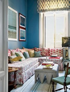 In the Naples, Italy, home of designer Allegra Hicks and entrepreneur Roberto Mottola di Amato, a banquette clad in a Bennison fabric is accented with large phulkari pillows and small pillows made of fabrics by Hicks; she also devised the ottoman's fabric and the carpet, which is by the Rug Company.