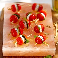 A Himalayan salt plate is used as a serving vessel. As the skewers sit, the water released from the tomatoes and mozzarella pulls salt out of the plate.