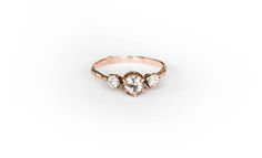This stunning ring features morganite and two forever one moissanite set in rose gold. Ring details-  -Thin 14k gold twig band, about 1.3mm. -Your choice of 14k white or yellow gold.  -Gemstones:  -Center stone is 5mm blush colored morganite.  -Side stones are 3mm forever one moissanite.  Please select your correct ring size from the drop down menu.  Feel free to let me know if you have any questions