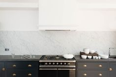 Black range | balck cabinetry | marble slab half splash | hood cover | deVOL Shaker Kitchen