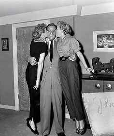 Lucy and Vivian Vance give John Wayne a smooch on the set of I Love Lucy.