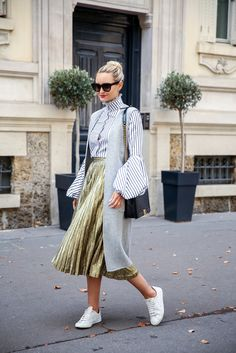 metallic pleated skirt styled with an exaggerated sleeve and sneakers for Paris fashion week