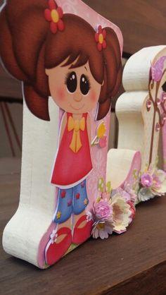 Nome  Lívia em MDF decorado com a  técnica de scrapdecor, letras  foradas com  papéis de scrapboook, flores feitas  a partir de  furadores. Menina  com  flores comprada  no site da silhuette Design. Linda menina  com  flores.