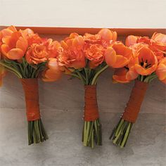 Brides: Orange Tulip Bridesmaid Bouquets. The bridesmaid bouquets included orange tulips and were wrapped in raw silk.
