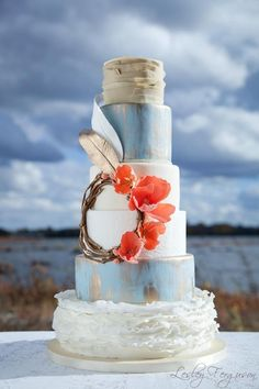 Rustic baby blue and white wedding cake with silvery gold feathers and coral flowers