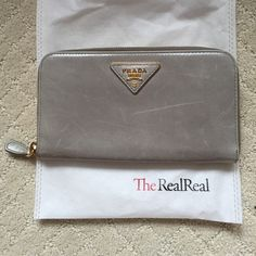 authentic prada zip around wallet in nube authenticated by both poshmark and the real real, selling because it's a tad large for me. feel free to ask any questions or for more pictures (-:    will take $180 on ♏️ercari Prada Bags Wallets