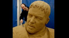 """Dieser überdimensionale Charakterkopf gehört Russell Crowe. Gewidmet ist die Skulptur seiner Darstellung des römischen Feldherren Maximus Decimus Meridius im Monumentalfilm """"Gladiator"""". Er und die anderen Filmstars sind aus einem riesigen, gemeinsamen Sandhaufen entstanden. """"Dann werden in großen Kästen abwechselnd Sand und Wasser geschichtet und mit sogenannten Rüttlern zusammengepresst"""", erklärt Pressesprecherin Bianca Lohr. """"Wenn die Masse getrocknet ist, werden mehrere dieser Kästen für…"""