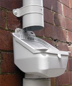 A photo of a leaf-shedding rain-head fitted to a downpipe against a brick wall. Water Collection System, Rain Collection, Water Plants, Cool Plants, Rain Barrel System, Water Catchment, Rain Head, Water From Air, Rainwater Harvesting System