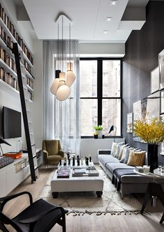 Double-height living room with built-in bookshelves high up on wall that are accessed by a ladder (I've always wanted a library tall enough that it requires a ladder!) Grey grasscloth-covered walls, tufted bench as ottoman and modern chandelier