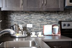 Stylish kitchhen. Dark shaker-style maple cabinets with glass mosaic tile backsplash and stainless steel appliances. At Prospect Rise townhomes by Avi Urban.