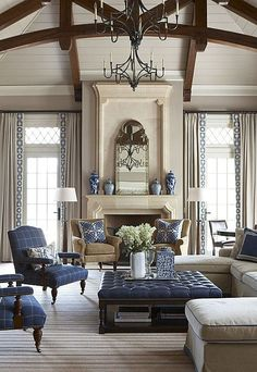 A high, vaulted ceiling with wrought iron chandeliers and an oversized tufted leather ottoman make this new traditional style living room stand out