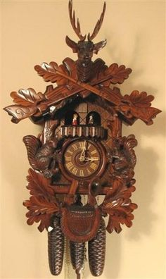Model #8361 Hunter's Cuckoo Clock with 3-D Free-standing Squirrels    This large and beautifully-carved cuckoo clock speaks of old-world charm and craftsmanship. The carving shows a still life of the life of a hunter. It's dimensional carvings include hunting trophies, live game (including beautifully carved squirrels holding acorns), a hunting horn, ammunition pouch, and guns, all surrounded by carved oak leaves.