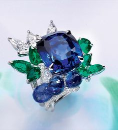 Handmade Sapphire, Emerald and Diamond Ring LaFleur Collection La Fleur With Multishape Emeralds 3,47 Cts. and with 5,49 Cts. of Round, Multi Shape and Briolette Diamonds and Sapphire Briolettes 7,93 Cts. and 1 Ceylon Sapphire modified brilliant step cut 20,90 Cts. certified by GRS MAKE AN ENQUIRY