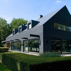 House in the Netherlands upgraded with a dark grey cladding of timber panels and tiles