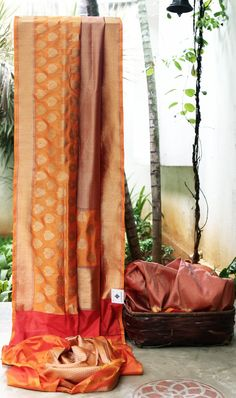 GLAMOROUS BURNT ORANGE WITH RED BENERAS SILK IS INTRICATELY WOVEN ALL OVER. THE BORDER HAS CLASSY MOTIFS WOVEN IN GOLD AND THE GRAND PALLU GIVES THE SAREE RAVISHED LOOK.