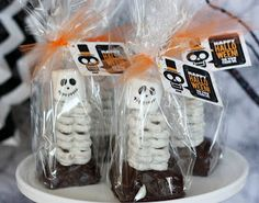 Cute Halloween treats!  Brownie and pretzel skeletons were a spooktacular edition. We made a pan of brownies in a square pan because we wanted them thick, cutting them into squares (don't forget to cut the edges off). Then covered them in ganache. Place a short bamboo skewer or sucker stick close to the back and pile white chocolate pretzels. Top with a marshmallow with a cute skeleton face (drawn on by editable markers) and package with our fun skeleton tag.