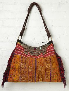 Hand embroidered hobo back with colorful yarn fringe trimming on each side. Top of front is trimmed with vintage metal necklaces with glass detailing and metal fringe embellishment. Top of bag zips close. Woven leather handle. Inside is fully lined with one zipper pocket.