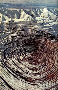 "Kennecott Copper mines bull's-eye in the Oquirrh Mountains stretches two and a half miles wide and more than half a mile deep - the nation's largest open-pit copper mine, and its most productive.""    From article Utah's Shining Oasis by Charles McCarry, photographs by James L. Amos 1975"