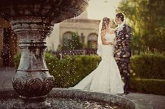 Stunning color photo of bride and groom through fountain, photo by Anika London Photography