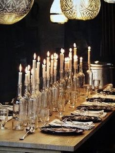 clear glass wine bottles of varying heights with candles as a long centerpiece