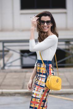 Look da Camila Coutinho, com blusa básica branca, bolsa amarela e saia colorida