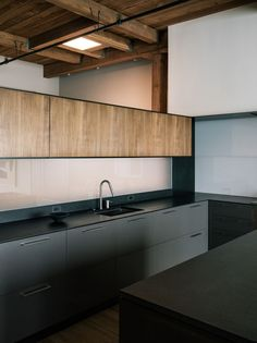 Line Office, San Francisco Loft, Photo by Joe Fletcher | Remodelista. In the kitchen area, a horizontal band of wood-faced cabinets sits above a glass backsplash that is lit from behind.