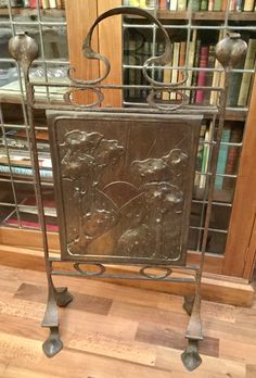 Ornate steel framed fire screen with central beaten oxidised copper panel depicting a  woodland scene