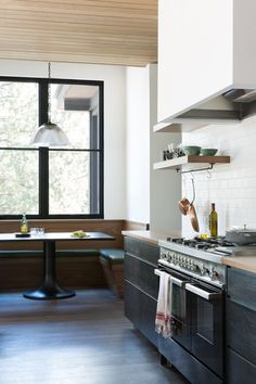 Kitchen, Range, Pendant Lighting, Wood Counter, Range Hood, Medium Hardwood Floor, Subway Tile Backsplashe, and Wood Cabinet A six-person breakfast banquette was crafted from walnut wood. The table was custom-made by ABD Studio and has a cold roll steel top with a turned wood base that has been ebonized black. The pendant light is vintage. Photo 8 of 20 in A Sleek Lake Tahoe Retreat Shows Off an Impressive Art Collection